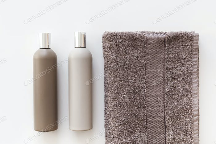 Plastic bottles of shampoo and body gel on towel isolated on white. Flat lay
