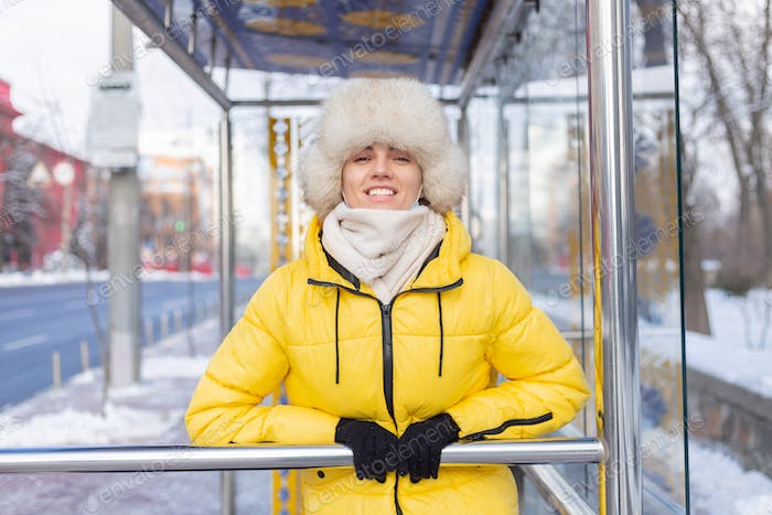 Woman in winter clothes on a cold day waiting for a bus at a bus stop