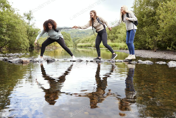 Three young adult women hold hands helping each other while carefully crossing a stream