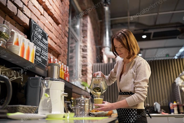woman or barmaid cooking smoothie at vegan cafe