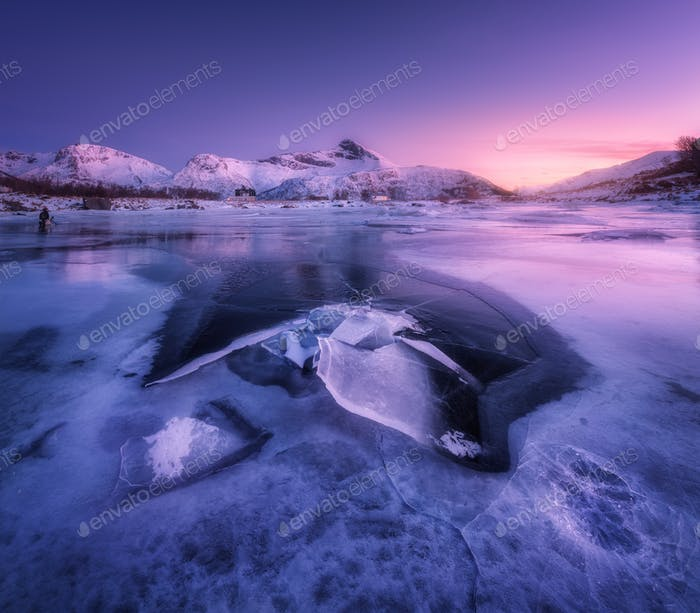 Snowy mountains, sea with frosty coast and purple sky