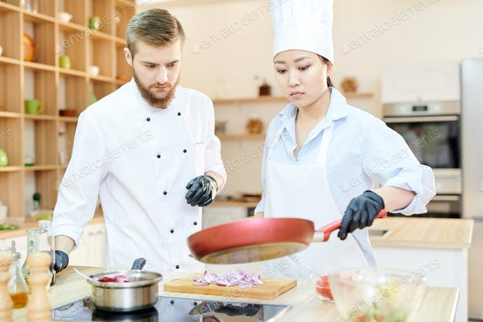 Two Professional Chefs at Work in Kitchen