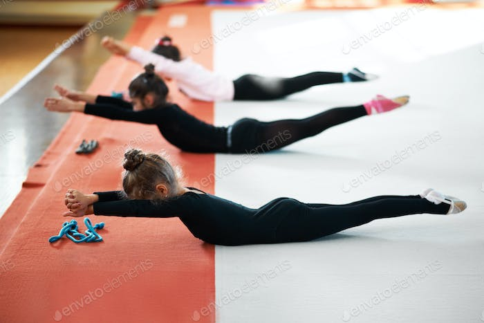 Children train back exercises in  gym