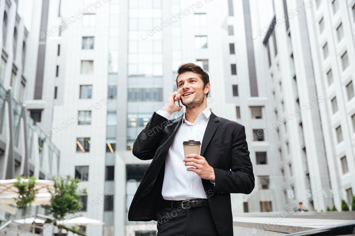 Cheerful young businessman talking on cell phone and drinking coffee