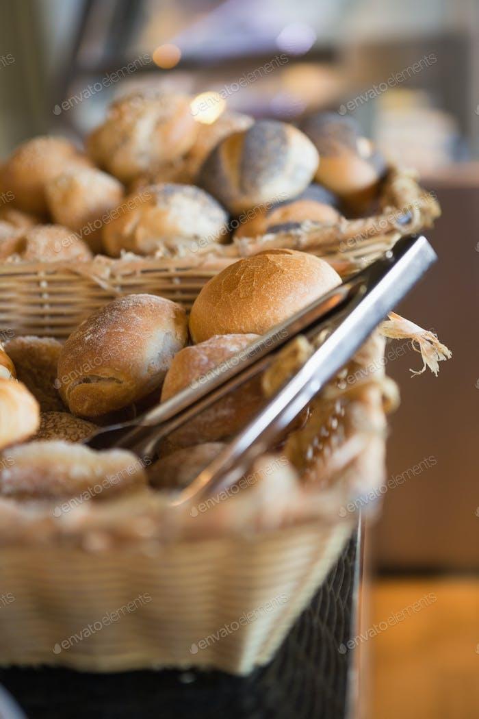 Korb mit frischem Brot und Zange in der Bäckerei
