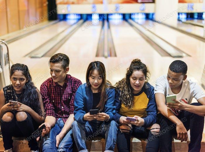 Gruppe von Teenager-Freunden mit Smartphone in einer Bowlingbahn