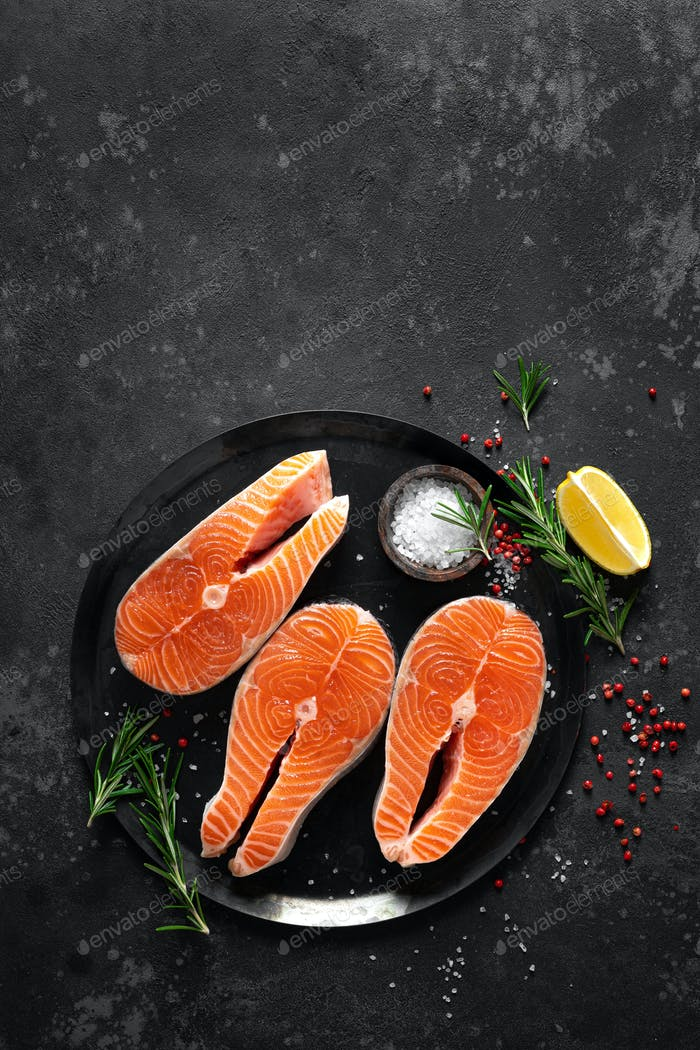 Fresh raw salmon fish steaks with cooking ingredients on kitchen table, healthy food