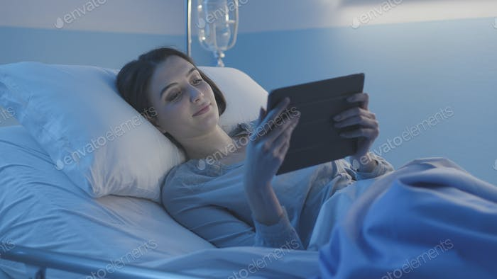 Young smiling patient lying in  bed and connecting with a tablet