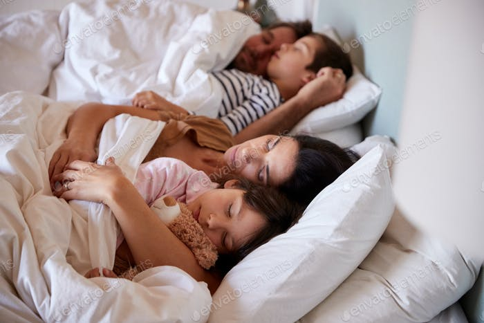 Mid adult parents sleeping in bed with their two young children, waist up, close up