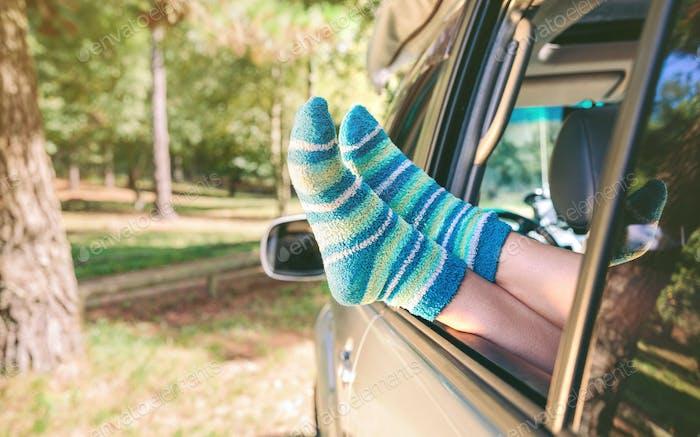 Female legs with socks resting over open window car