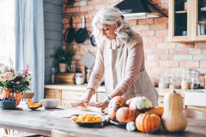 Frau in weißen Schürzen bereiten schmackhaftes Abendessen vor.