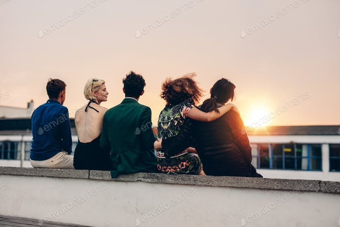 Friends relaxing on terrace in evening