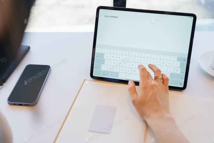 Woman fingers typing inscription on digital tablet