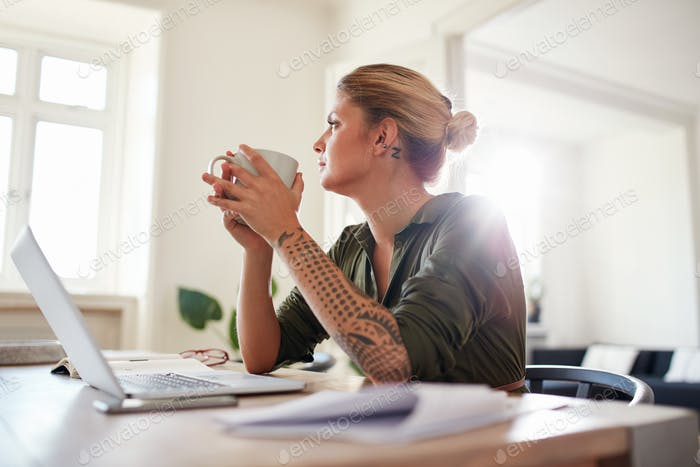 Young woman with coffee looking away and thinking