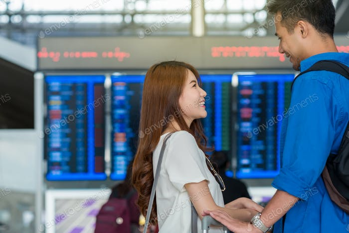 Asian couple traveler checking the flight with excited feeling at the travel information screen