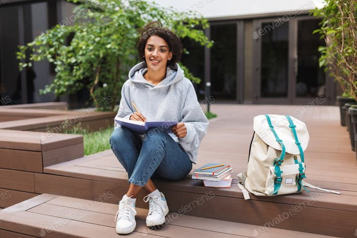 Beautiful lady sitting with books and making notes in notebook while happily looking in camera