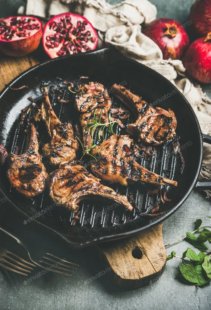 Grilled lamb meat chops served with fresh pomegranates and mint
