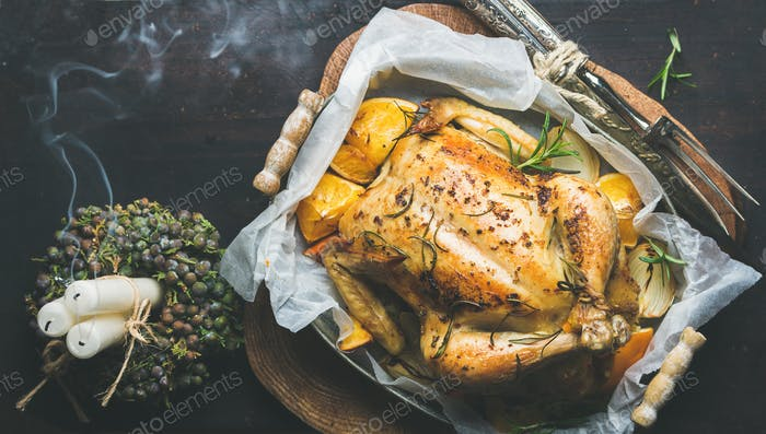 Christmas dinner with roasted chicken, rosemary and candle smoke