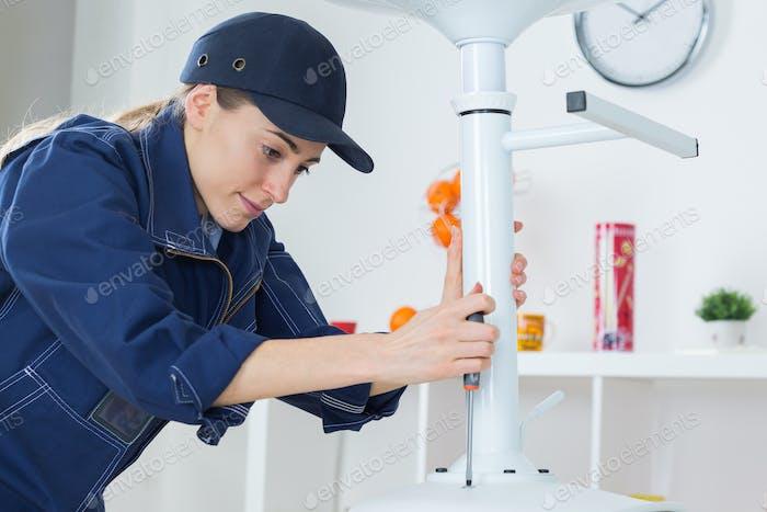 Female worker using screwdriver