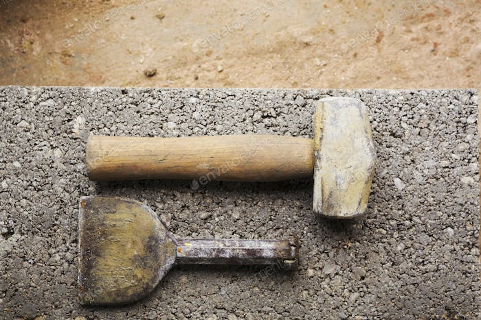 Close up of a hammer and chisel on a concrete slab.