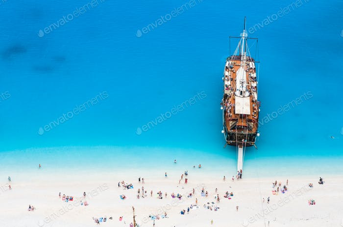 large sail cruise ship anchored at white sand beach