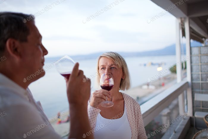 Couple Drinking Red Wine on Balcony of Beach Hotel