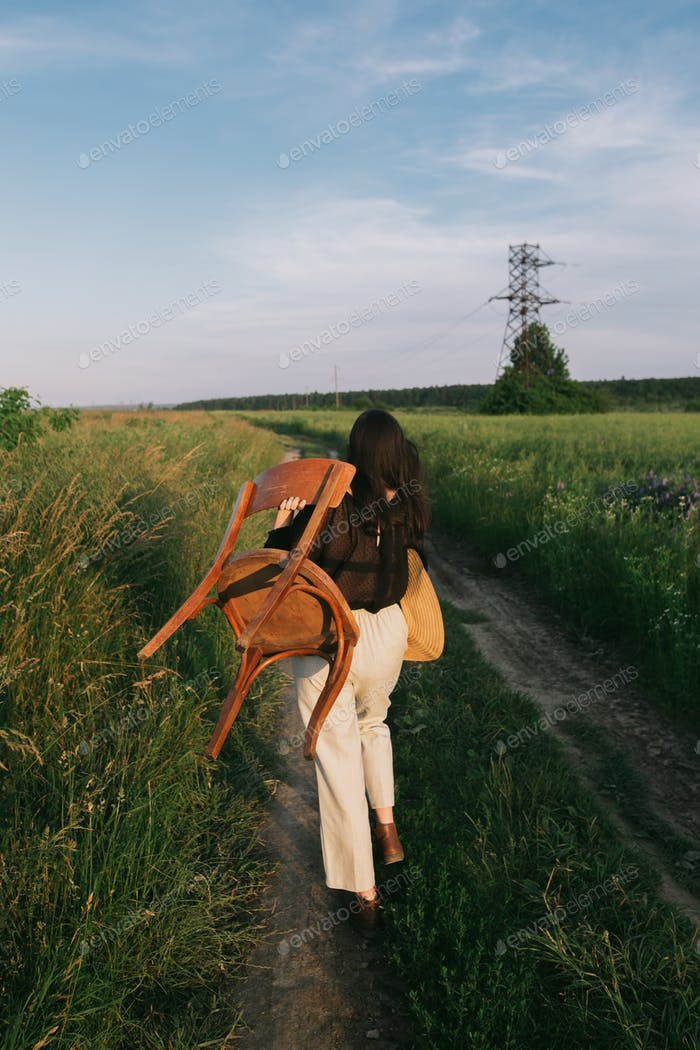 Stylish elegant girl carrying rustic chair, walking in summer field in sunset