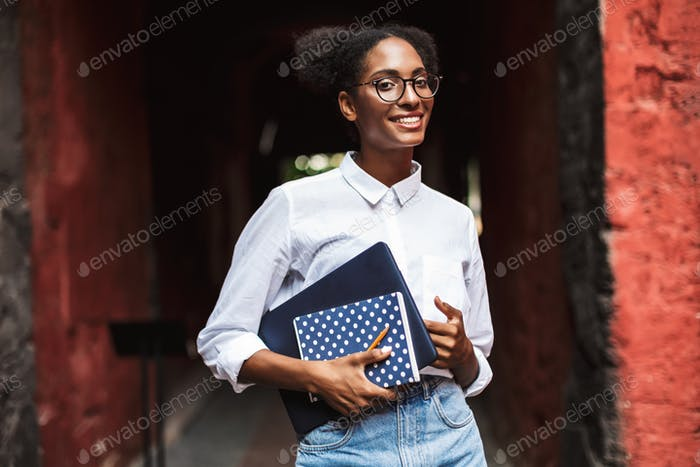 Nice african girl in eyeglasses and shirt holding laptop and not