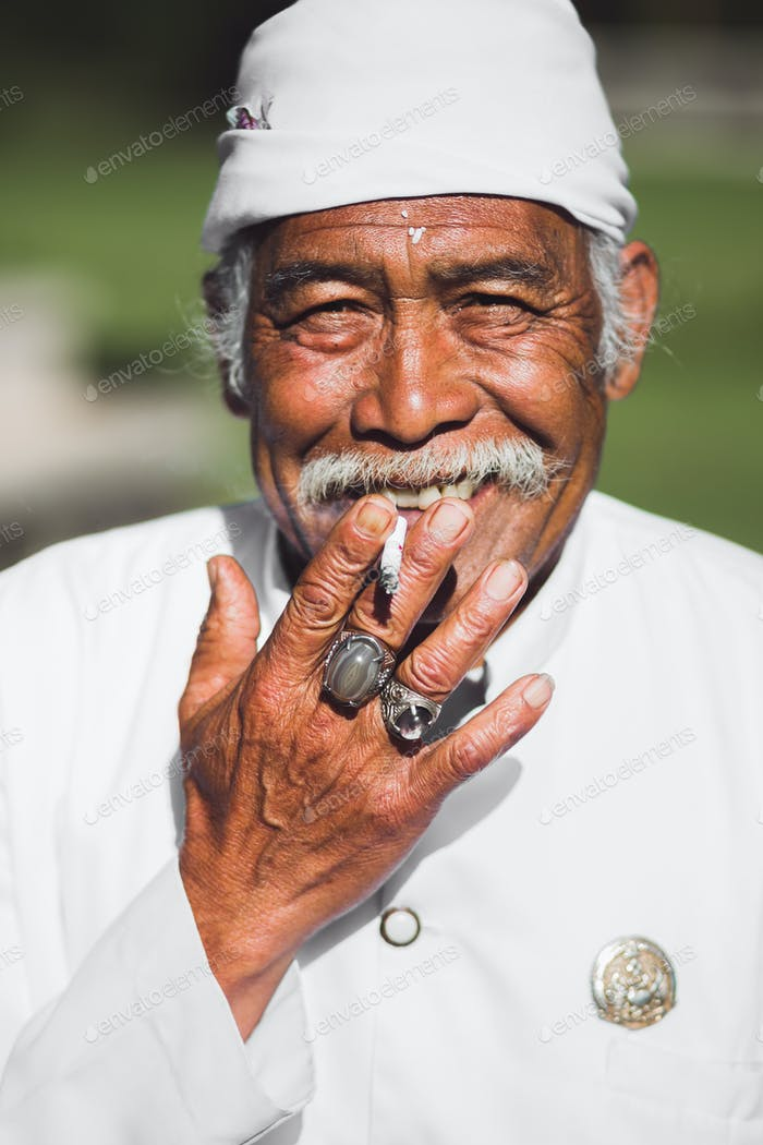 Balinese holy man with a mustache smokes and smiles in traditional white clothes