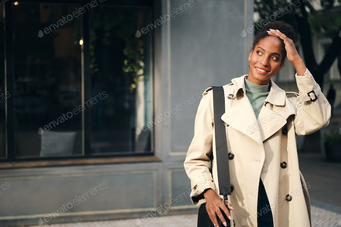 Beautiful casual African American girl in stylish trench coat happily looking away on city street