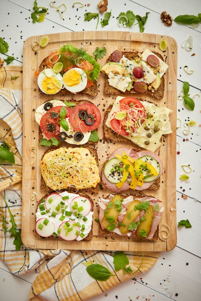 Colorful, different kinds sandwiches served on wooden chopping board. Vegetable toppings