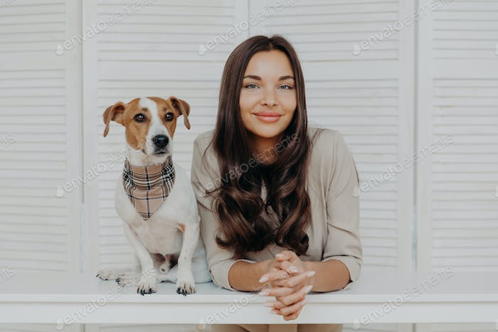 Good looking woman with dark hair, spends leisure time with dog, loves animals
