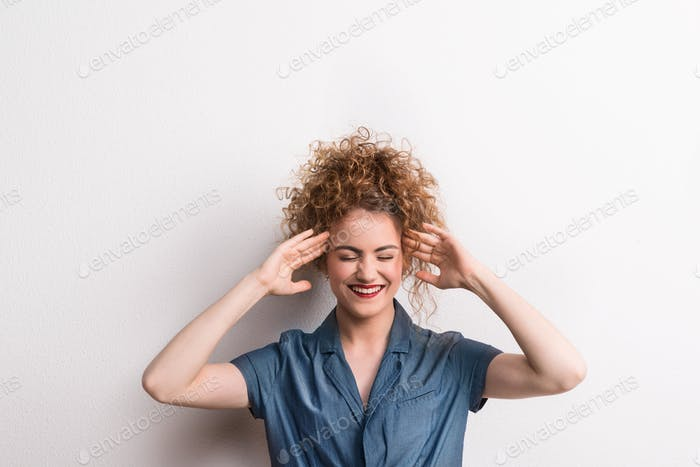 Young beautiful happy woman in studio, hands on temples.