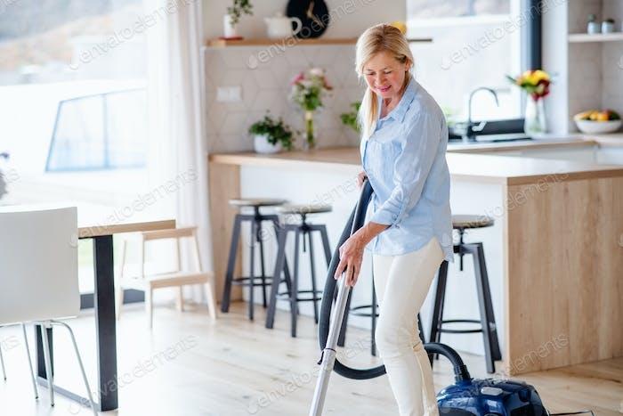 Porträt von Senior Frau mit Staubsauger drinnen zu Hause, Hoover