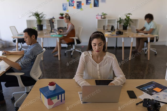 Businesswoman working on laptop at her desk