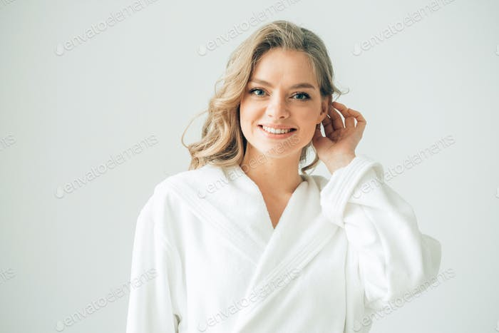 Woman in bath robe over white background, beautiful female with blonde hair beauty concept