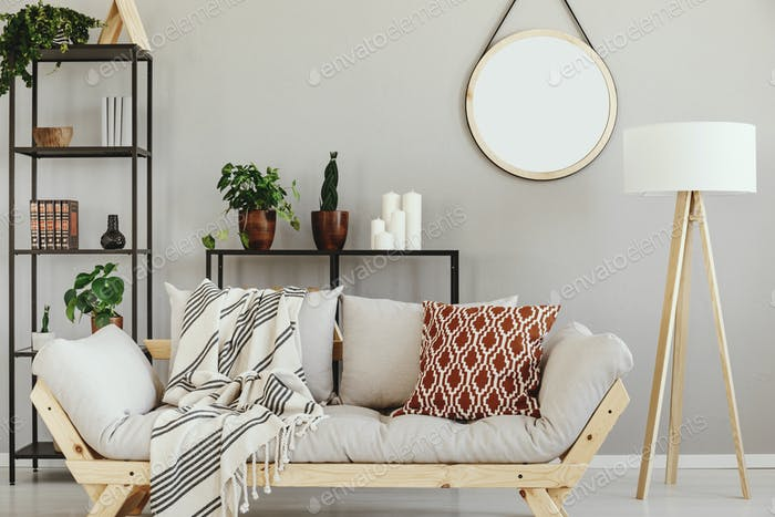 White wooden lamp next to stylish scandinavian couch with patter