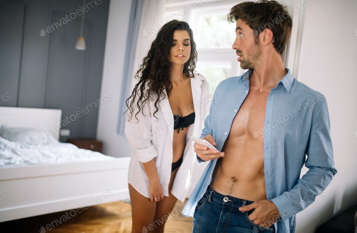 Wife with curiosity looking at husband talking privately on mobile