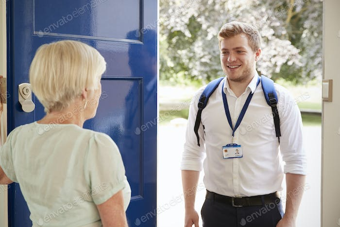 Senior woman greeting male care worker making home visit