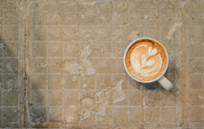 Latte coffee heart texture on concrete background.
