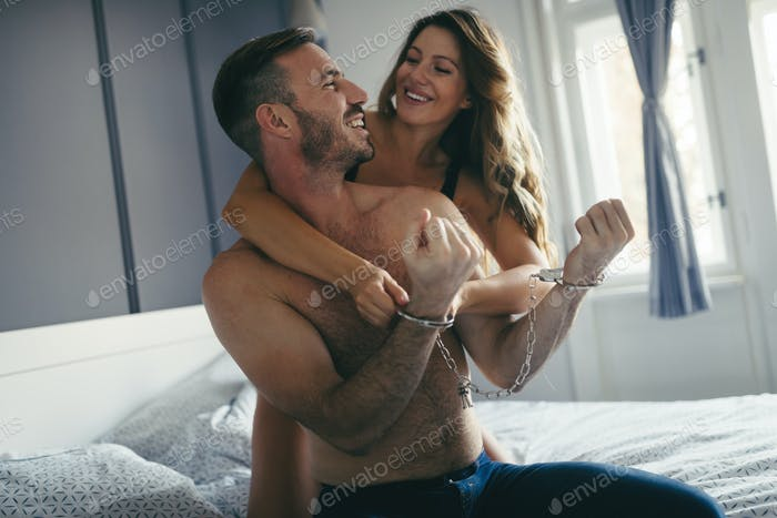 Woman and man playing domination games in bed