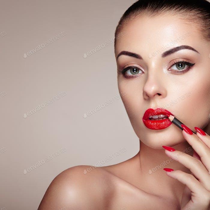 Schöne Frau malt Lippen mit Lippenstift