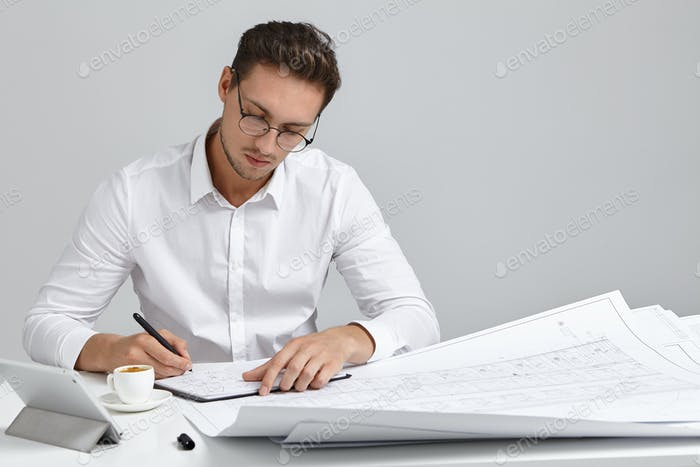 Talented young European bearded chief engineer wearing round glasses and white formal shirt sitting