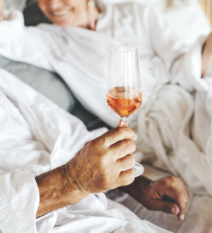 Paar mit Prosecco im Bett
