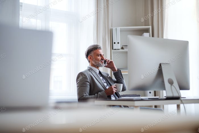 Businessman with smartphone, coffee and computer sitting at the table, making a phone call.