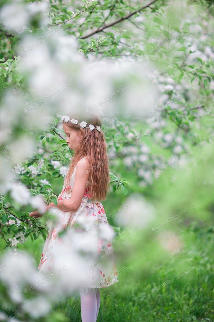 Little cute girl in blooming cherry garden outdoors