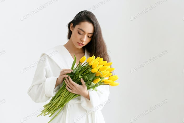 Frau mit Tulpen. Junge Brünette Mädchen mit gelben Blumen Tulpe