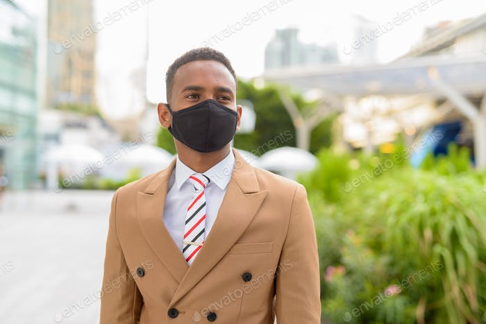 Young African businessman thinking with mask for protection from corona virus outbreak in the city