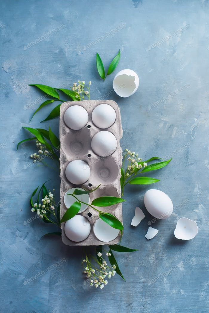 Chicken eggs, whole and broken, in a paper packaging on a concrete background with green leaves and