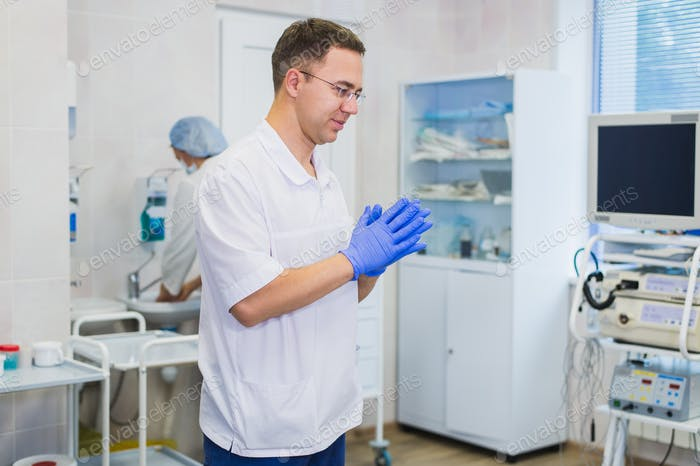 Handsome mature surgeon in blue medical wear and mask is putting on medical gloves at operating room
